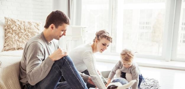 Szczęśliwa rodzina bawi się z psem w przestronnym salonie