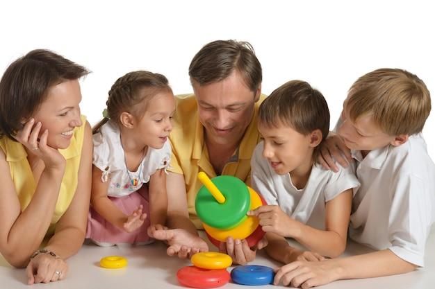 Szczęśliwa rodzina bawi się zabawką, na białym tle