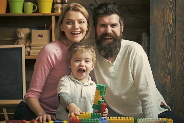 Szczęśliwa rodzina bawić się razem. podekscytowany dzieciak siedzi między uśmiechniętymi rodzicami. mama i tata śmieją się, podczas gdy dziecko bawi się klockami konstrukcyjnymi.