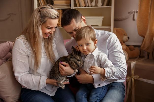 Szczęśliwa rodzina bawić się z wielkanocnym królikiem i świętuje wielkanocny dzień