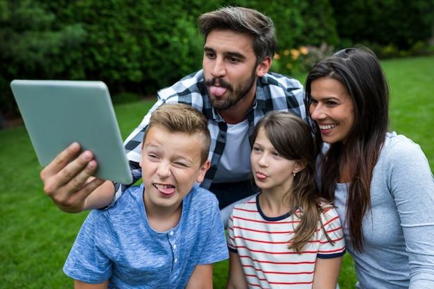 Szczęśliwa rodzina bierze selfie od cyfrowej pastylki w parku