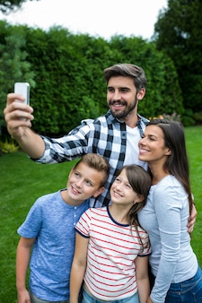 Szczęśliwa rodzina bierze selfie od telefonu komórkowego w parku