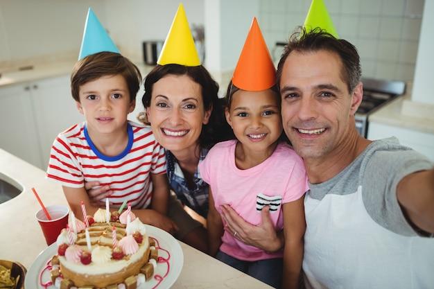 Szczęśliwa rodzina bierze selfie podczas świętowania urodzin