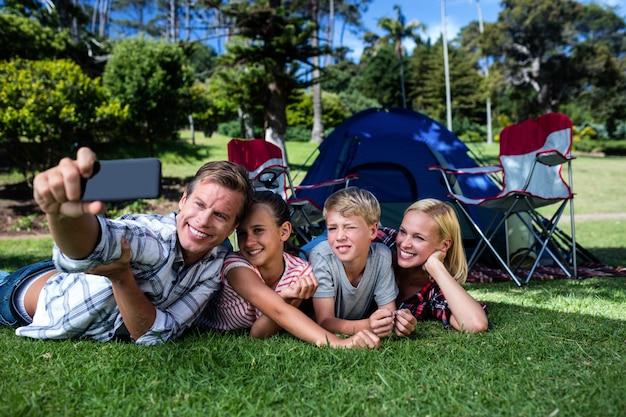 Szczęśliwa rodzina bierze selfie w parku