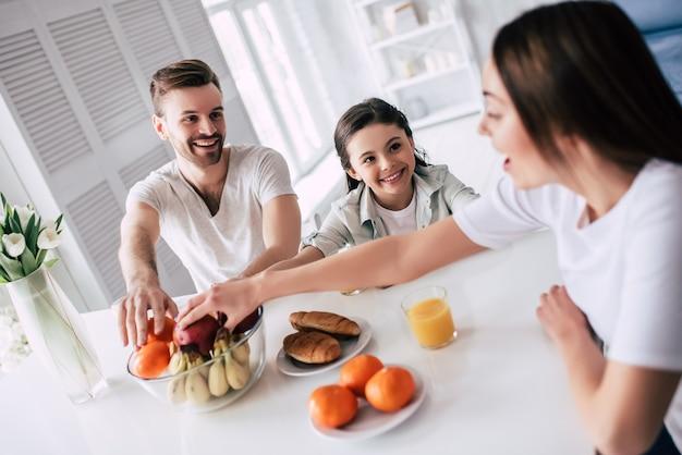 Szczęśliwa rodzina biorąc jabłka na stół