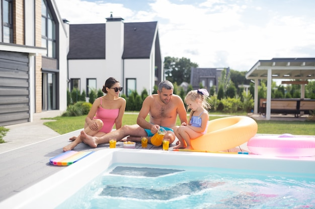 Szczęśliwa rodzina chłodzenie. szczęśliwa rodzina czuje się zrelaksowana podczas relaksu przy basenie w upalny letni dzień?