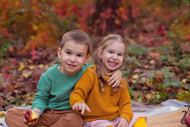 Szczęśliwa rodzina, chłopiec, dziewczynka je ciasto na jesienny piknik z dynią, jabłkami, herbatą