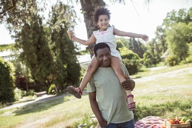 Szczęśliwa rodzina. ciemnoskóry uroczy dzieciak siedzący na ramionach taty