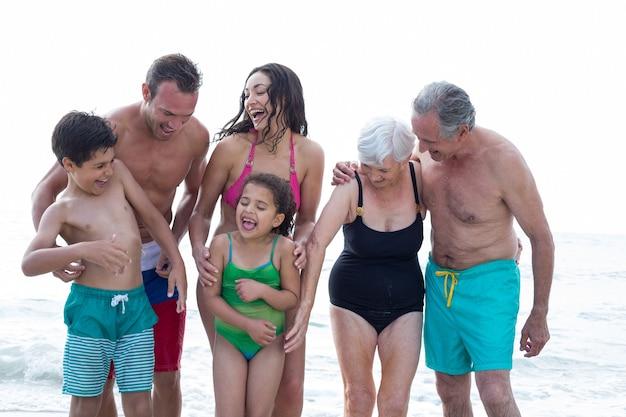 Szczęśliwa rodzina, ciesząc się na brzegu morza na plaży