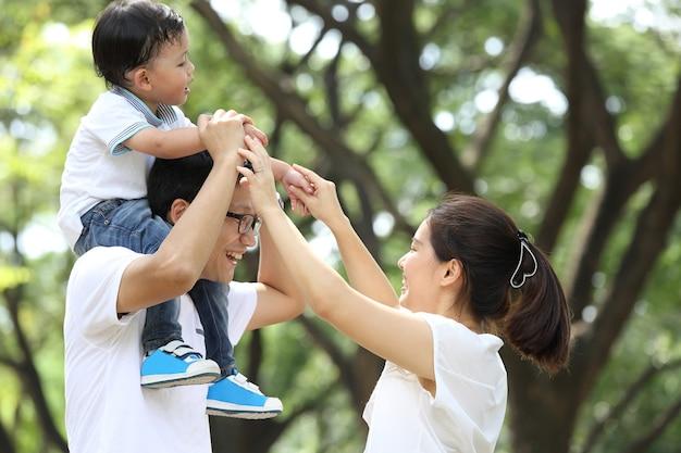 Szczęśliwa rodzina cieszy się i ćwiczy razem w ogrodzie.