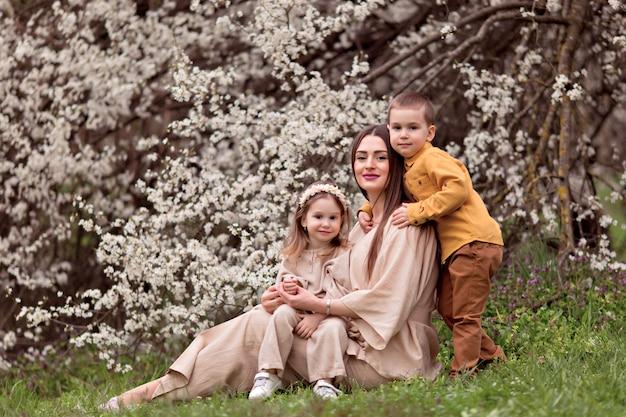 Szczęśliwa rodzina, ciężarna mama, córka i syn na tle kwitnących drzew.