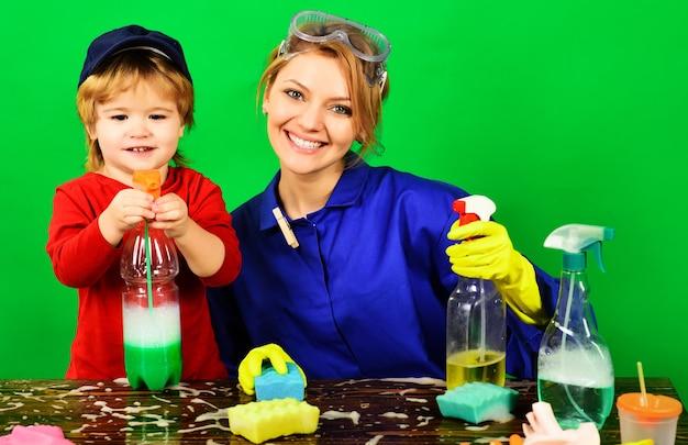 Szczęśliwa rodzina czas sprzątania matka i syn ze środkami czyszczącymi uśmiechnięta kobieta i dziecko bawią się