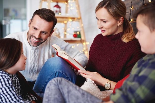Szczęśliwa rodzina czytając książkę w czasie świąt bożego narodzenia