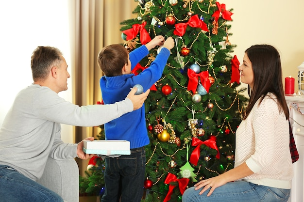 Szczęśliwa rodzina dekoruje choinkę w wakacyjnym salonie