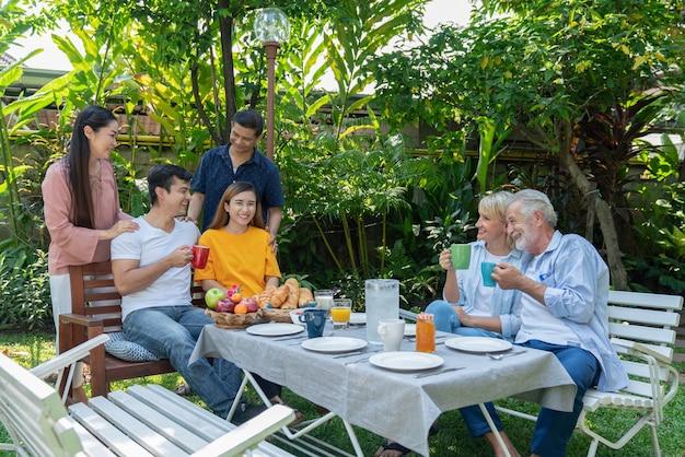 Szczęśliwa rodzina dobrze się bawić, jedząc rano razem śniadanie w przydomowym ogrodzie