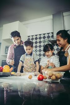 Szczęśliwa rodzina dobrze się razem gotuje w kuchni w domu. pojęcie rodziny.