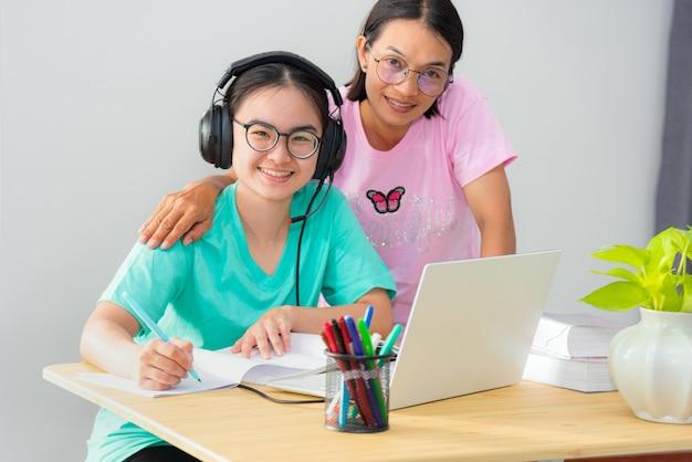 Szczęśliwa rodzina dwa azjatka patrząc w górę matka rodzic jest nauczycielem porada instrukcja córka nastolatka studentka nauka online korzystanie z laptopa edukacja z klasy uniwersyteckiej nauka w domu