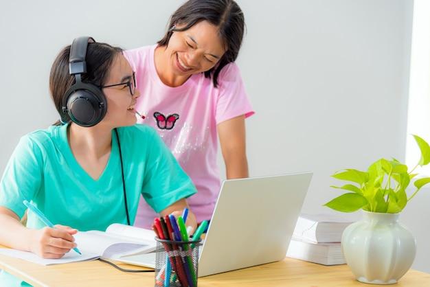 Szczęśliwa rodzina dwa azjatki kobieta matka rodzic jest nauczycielem porada instrukcja córka nastolatka studentka online nauka ze szkoły korzystanie z laptopa edukacja z klasy uniwersyteckiej nauka w domu