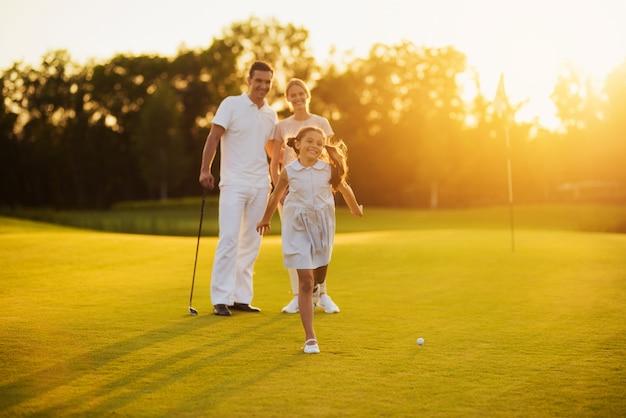 Szczęśliwa rodzina golfistów na kursie radośni gracze.