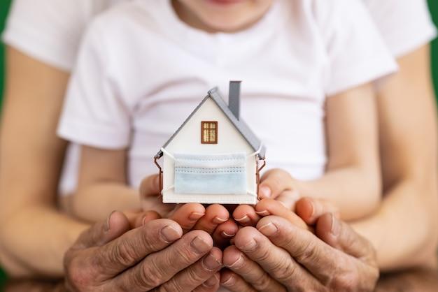 Szczęśliwa rodzina gospodarstwa dom z maską ochronną. biznes podczas koncepcji pandemii koronawirusa covid-19
