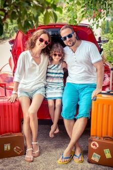 Szczęśliwa rodzina gotowa do podróży ludzie stojący w pobliżu czerwonego samochodu letnie wakacje i koncepcja podróży