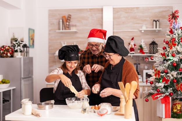 Szczęśliwa rodzina gotuje domowy deser piernikowy, robiąc tradycyjne ciasto