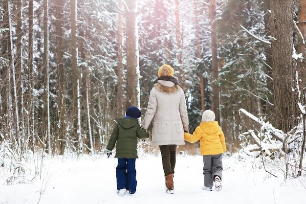 Szczęśliwa rodzina gra i śmieje się zimą na zewnątrz w śniegu. zimowy dzień w parku miejskim.