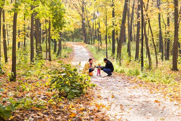 Szczęśliwa rodzina gra przeciwko niewyraźnym żółtym liściom w jesiennym parku