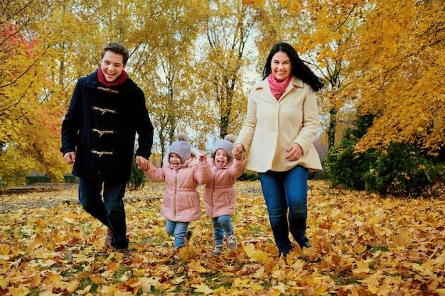 Szczęśliwa rodzina gra w jesień parku.