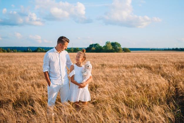 Szczęśliwa rodzina gra w polu pszenicy