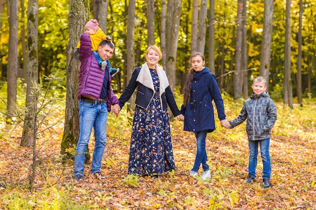 Szczęśliwa rodzina gra z jesiennych liści w parku