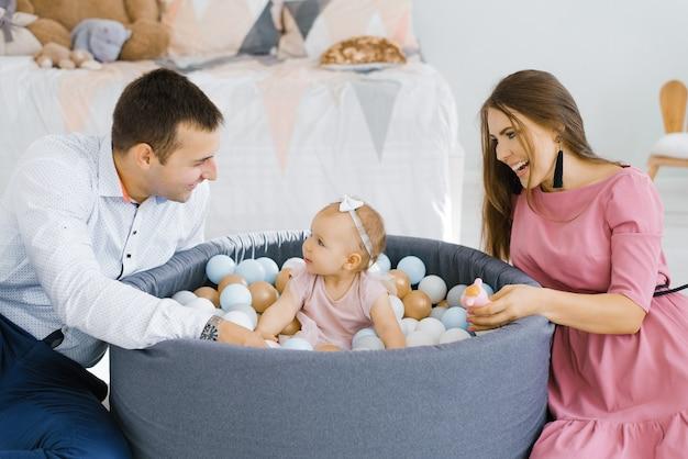 Szczęśliwa rodzina gra z kolorowych balonów w pokoju dziecięcym w domu