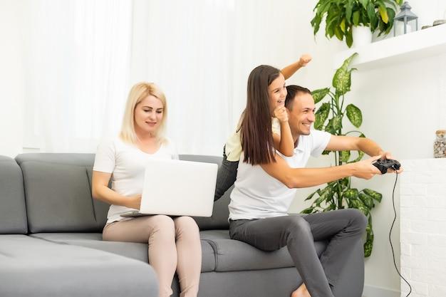 Szczęśliwa rodzina grając w gry wideo w domu i wspólnie się bawiąc.