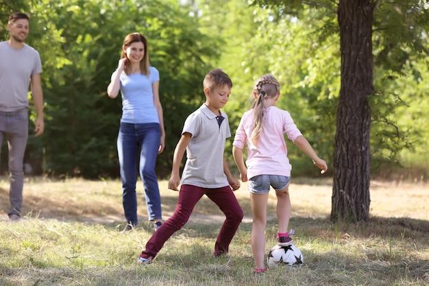 Szczęśliwa rodzina grająca w piłkę nożną na świeżym powietrzu