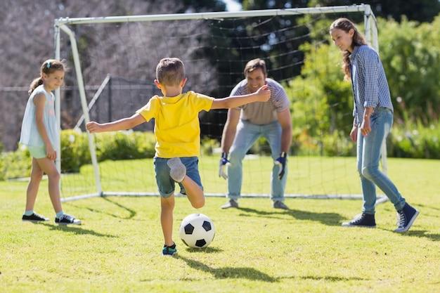 Szczęśliwa rodzina gry w piłkę nożną w parku