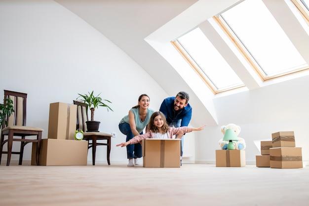 Szczęśliwa rodzina i dzieci bawiące się z kartonów w nowym domu na dzień przeprowadzki.