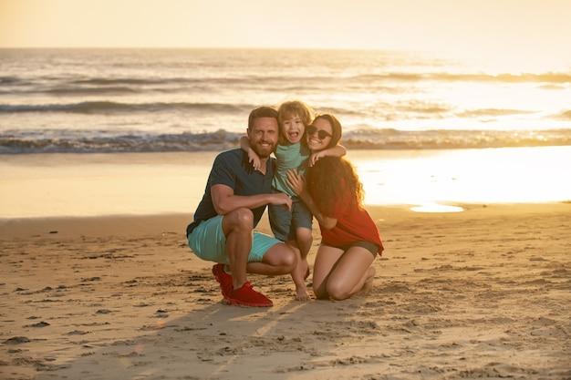 Szczęśliwa rodzina i dziecko cieszące się zachodem słońca w letnim wypoczynku na plaży