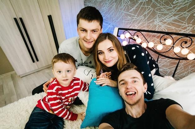 Szczęśliwa rodzina i przyjaciele robią selfie w wigilię bożego narodzenia w swetrach świętego mikołaja, grają w girlandę na łóżku w domu. cieszyć się miłością, wakacjami. wesołych świąt i szczęśliwego nowego roku.