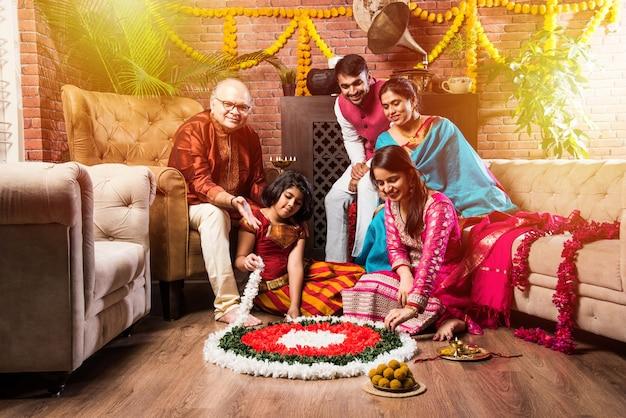 Szczęśliwa rodzina indyjska świętowanie diwali lub hinduskiego festiwalu powitanie lub wykonywanie pooja i jedzenie słodyczy w tradycyjnym stroju w domu ozdobionym kwiatami nagietka