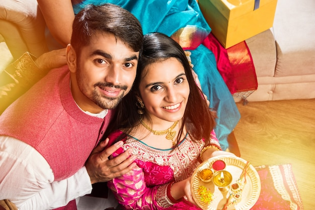Szczęśliwa rodzina indyjska świętowanie hinduskich świąt powitanie lub wykonywanie pooja i jedzenie słodyczy w tradycyjnym stroju w domu ozdobionym kwiatami nagietka