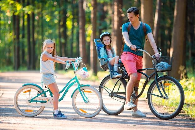 Szczęśliwa rodzina jechać na rowerze outdoors przy parkiem
