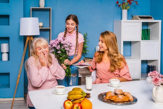 Szczęśliwa rodzina jedząc śniadanie rano w domu i świętując urodziny