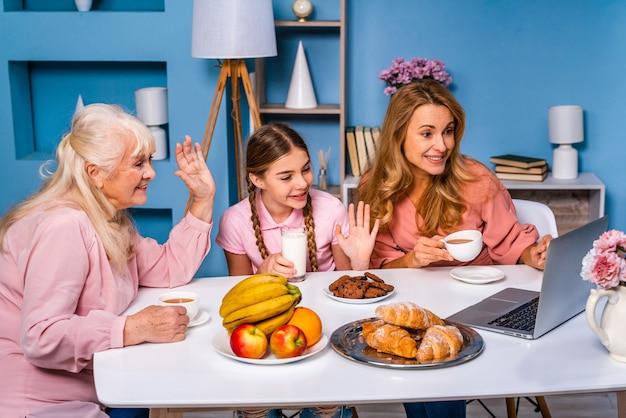 Szczęśliwa rodzina jedząc śniadanie rano w domu mając wideokonferencję