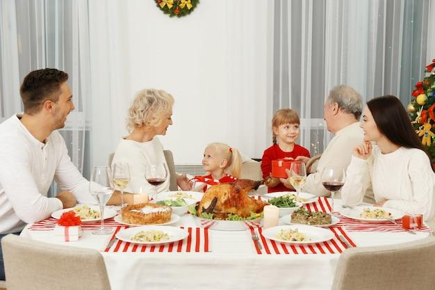 Szczęśliwa rodzina jedząca obiad dziękczynny w salonie?