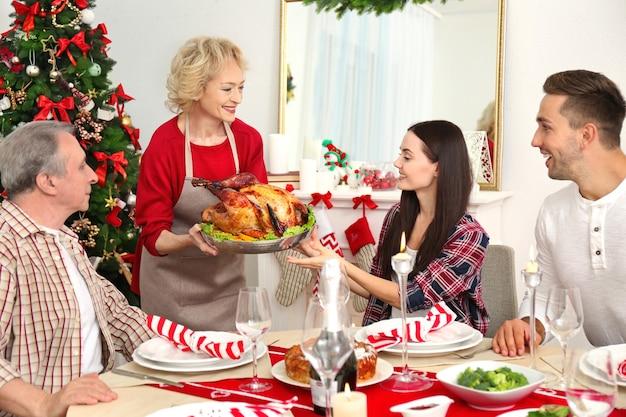 Szczęśliwa rodzina jedząca świąteczny obiad w salonie