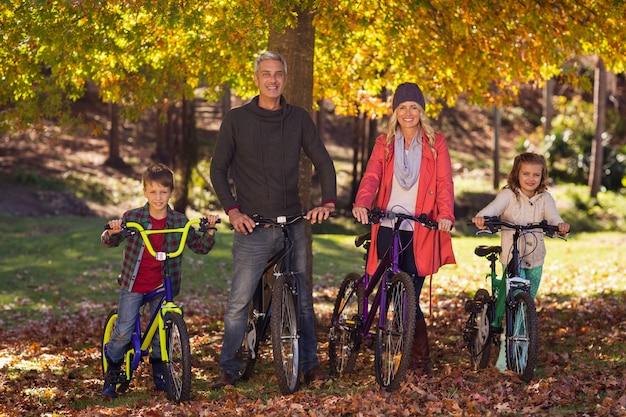 Szczęśliwa rodzina jedzie bicykle przy parkiem