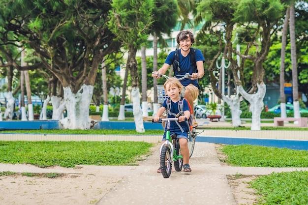 Szczęśliwa rodzina jedzie na rowerach na zewnątrz i uśmiecha się