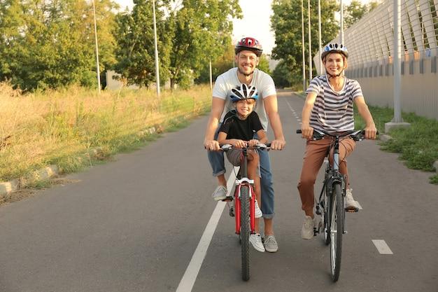 Szczęśliwa rodzina jedzie na rowerach na zewnątrz