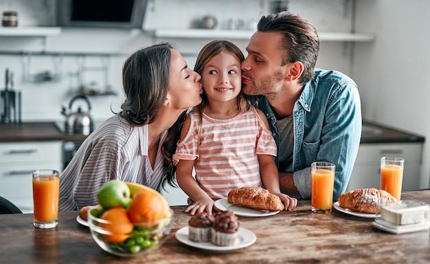 Szczęśliwa rodzina koncepcja w kuchni. mama i tata całują córkę, przygotowując się do pysznego śniadania.