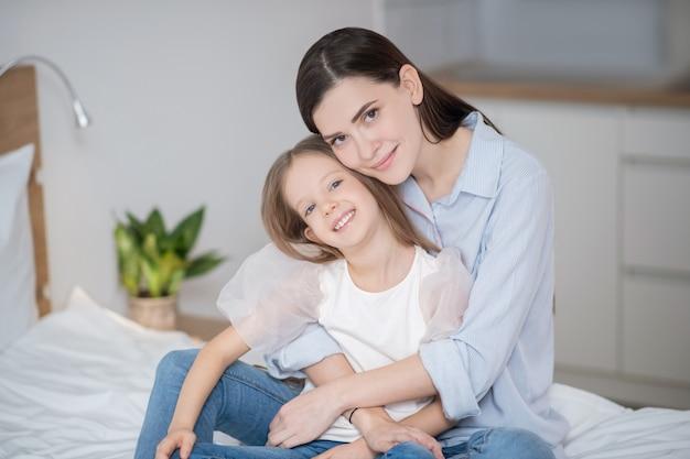 Szczęśliwa rodzina. ładna kobieta przytula córkę i wygląda na szczęśliwą